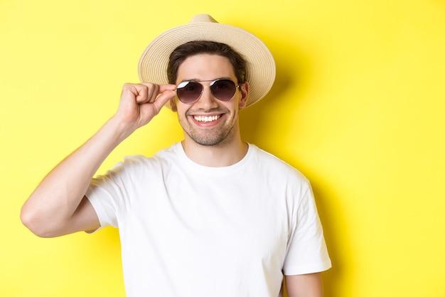 Concept van toerisme en vakantie. close-up van een knappe toerist die er gelukkig uitziet, een zonnebril en een zomerhoed draagt, die over een gele achtergrond staat