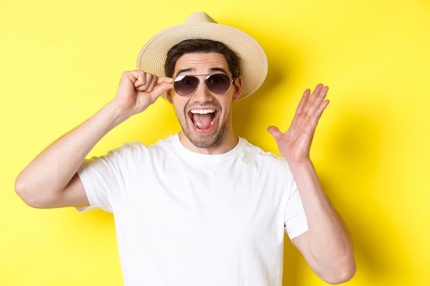 Concept van toerisme en vakantie. close-up van verrast man schreeuwen van vreugde, genieten van vakantie, zonnebril met zomerhoed, gele achtergrond dragen.