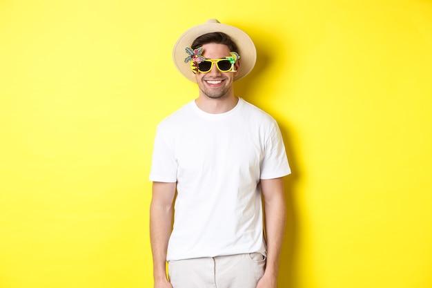 Concept van toerisme en vakantie. ontspannen lachende man genieten van avondmaal reis, zonnebril en strooien hoed, gele achtergrond dragen.