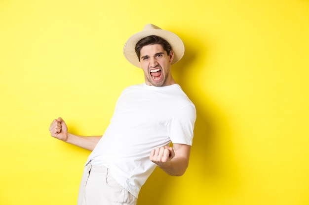 Concept van toerisme en vakantie. tevreden jonge mannelijke toerist die viert, iets wint en zich verheugt, vuistpomp maakt en ja schreeuwt, staande tegen een gele achtergrond.
