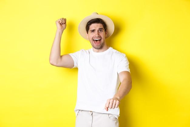 Concept van toerisme en zomer. jongeman reiziger die rodeo gebaar toont, staande in strohoed en witte kleren, staande over gele achtergrond