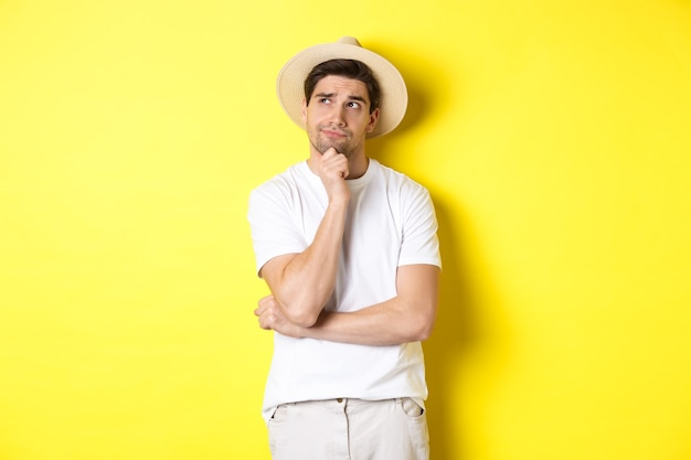 Concept van toerisme en zomer. nadenkende man toerist nadenken, kijken naar de linkerbovenhoek en denken, staande in strooien hoed en wit t-shirt tegen gele achtergrond.