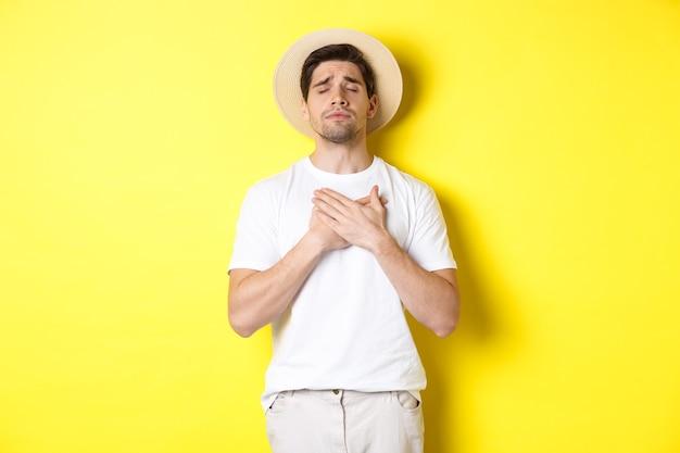 Concept van toerisme en zomer. romantische man met strohoed die er nostalgisch uitziet, ogen dicht en handen op het hart houdt, staande tegen een gele achtergrond.