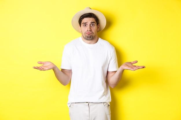 Concept van toerisme en zomer. verward mannelijke toerist die zijn schouders ophaalt, besluiteloos kijkt, tegen een gele achtergrond staat.