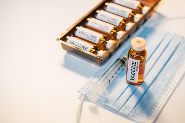 Concept van vaccinatie tegen coronavirus. fles vaccin op blauw medisch masker, spuit en doos met ampullen, witte tafel, selectieve aandacht. belettering op het etiket covid-19. kopieer ruimte.