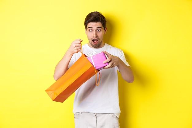 Concept van vakantie en feest. jonge man die verrast kijkt als een cadeau uit een boodschappentas, staande over een gele achtergrond.