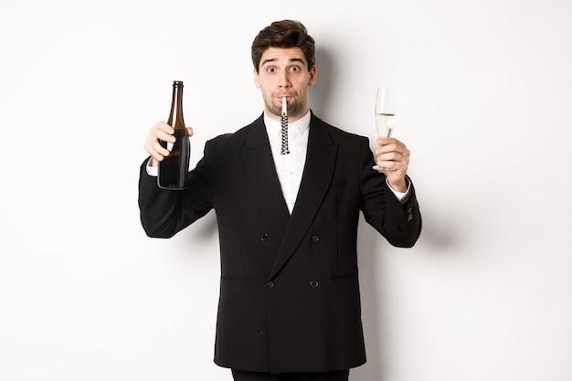 Concept van vakantie, feest en feest. portret van een knappe jongen in een zwart pak, een fles champagne en glas grootbrengend, een feestfluitje blazen, een verjaardag hebben, op een witte achtergrond staan