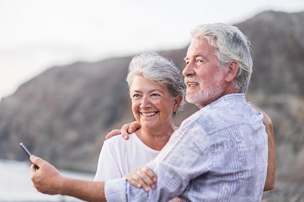 Concept van vakantie, technologie, toerisme, reizen en mensen - gelukkig senior koppel met mobiele telefoon op kiezelstrand lachen en grappen knuffelen en foto maken.
