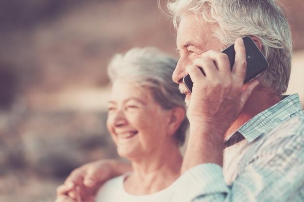 Concept van vakantie, technologie, toerisme, reizen en mensen - gelukkig senior koppel met mobiele telefoon op telefoon op kiezelstrand lachen en grappen maken. wit haar
