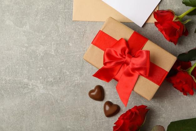 Concept van valentijnsdag met geschenkdoos en rozen op grijze achtergrond