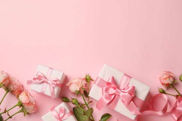 Concept van valentijnsdag met geschenkdozen en rozen op roze achtergrond