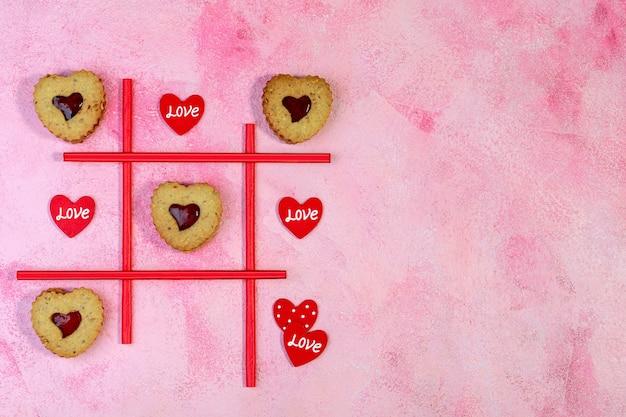 Concept van valentijnsdag met hartjes linzer koekjesspel van tic-tac-toe