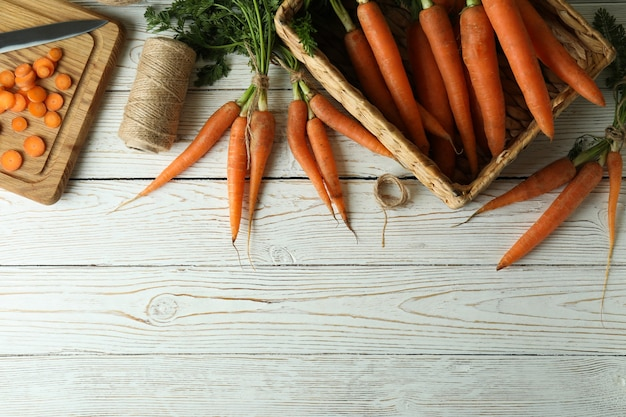 Concept van verse groente met wortel op witte houten oppervlak