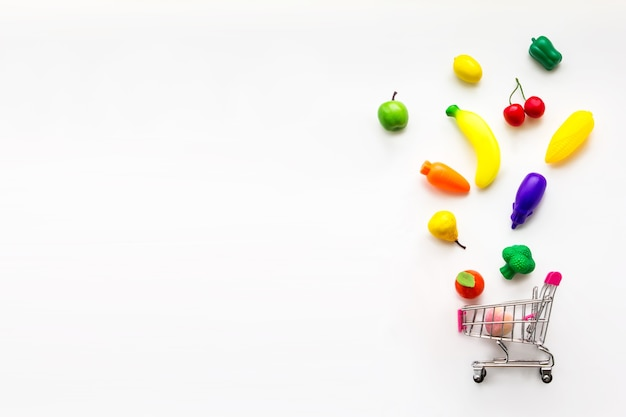 Concept van voedsel en dieet. mini speelgoed biologische groenten en fruit vallen in mini-winkelwagentje