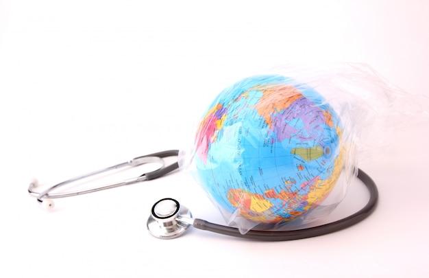 Concept van wereldmilieudag. aarde in een plastic zak met een stethoscoop op wit