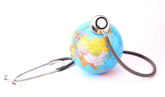 Concept van wereldmilieudag. aarde met een stethoscoop op wit wordt geïsoleerd