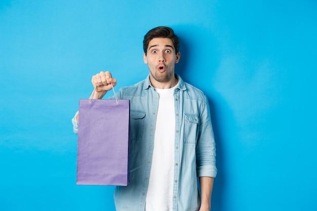 Concept van winkelen, vakantie en levensstijl. knappe verraste kerel die een papieren zak uit de winkel vasthoudt en verbaasd kijkt, staande over een blauwe achtergrond