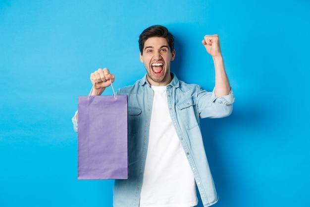 Concept van winkelen, vakantie en levensstijl. vrolijke jongeman viert feest, houdt papieren zak vast en maakt vuistpomp als winnaar, staande over blauwe achtergrond