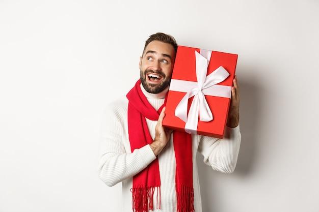 Concept van wintervakantie. gelukkige man die geschenkdoos schudt om te raden wat erin zit, nieuwsgierig kijkt, kerstcadeautjes ontvangt, staande op een witte achtergrond.