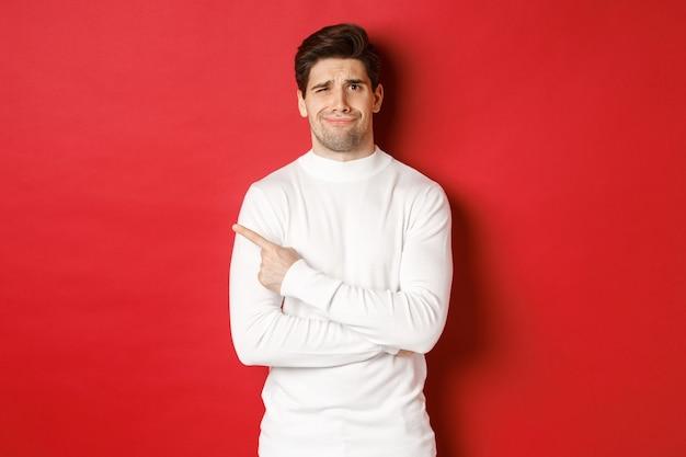 Concept van wintervakantie kerst en lifestyle beeld van sceptische jonge man in witte trui don...
