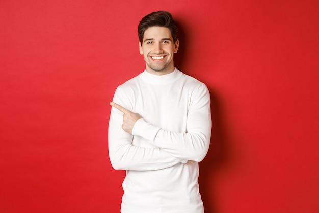 Concept van wintervakantie kerst en lifestyle portret van aantrekkelijke man in witte trui punt...