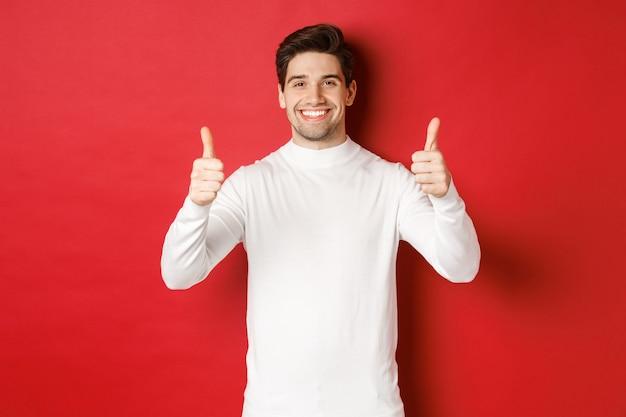 Concept van wintervakantie kerst en lifestyle portret van tevreden knappe man in wit zweet...