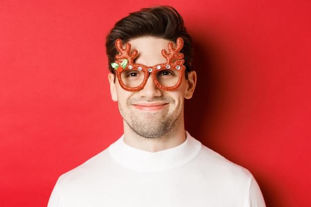 Concept van wintervakantie, kerstmis en feest. close-up van aantrekkelijk lachend mannelijk model in feestbril, staande tegen rode achtergrond