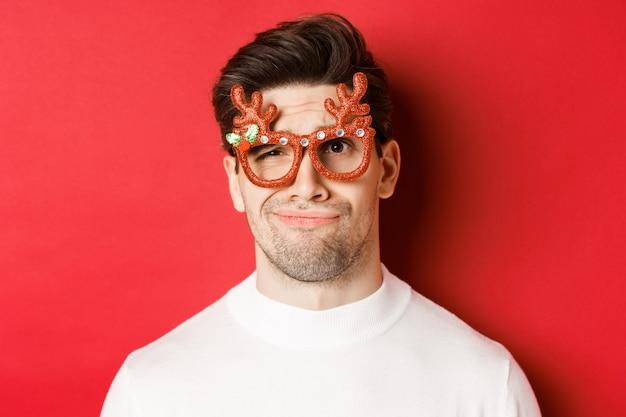 Concept van wintervakantie, kerstmis en feest. close-up van een sceptische knappe man met een feestbril, die er twijfelachtig en ongeamuseerd uitziet, staande tegen een rode achtergrond
