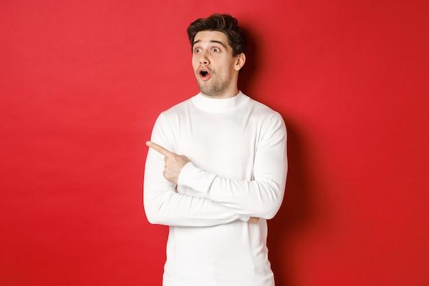Concept van wintervakantie portret van onder de indruk knappe man in witte trui wijzend en kijkend