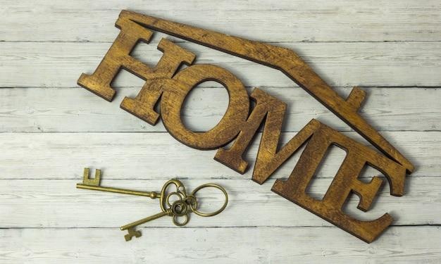 Concept van woningverwerving, de sleutel en het woord huis op een houten achtergrond