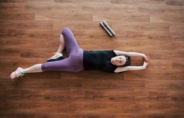 Concept van yoga en fitness zwangerschap. portret van een jong model van een zwangere vrouw die zich binnenshuis ontwikkelt.