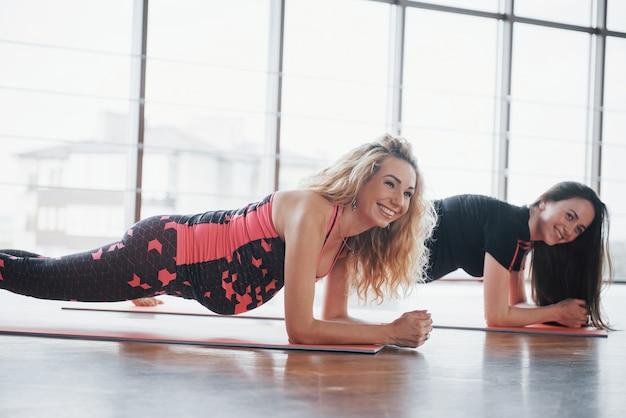 Concept van yoga en fitness zwangerschap. portret van een jong model van zwangere yoga dat binnenshuis wordt ontwikkeld.