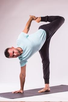Concept van yoga. knappe man doet yoga oefening geïsoleerd op een witte achtergrond