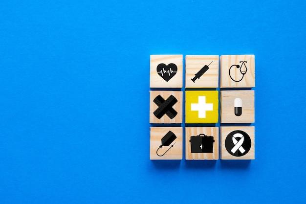 Concept van ziektekostenverzekering, houten blokken met blauwe medische symbolen, kopieer ruimte