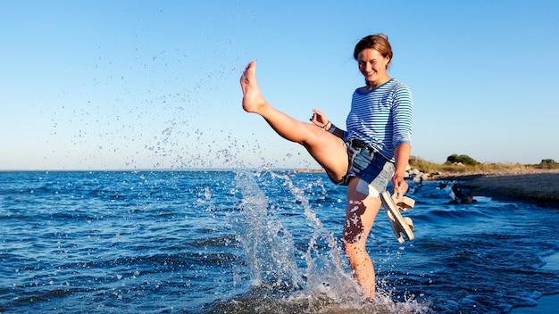 Concept van zomervakantie op zee en live-stijl. een jonge donkerharige vrouw lacht, loopt langs het strand, speelt met golven, sproeit veel en geniet van de felle zon op een zomerse dag.