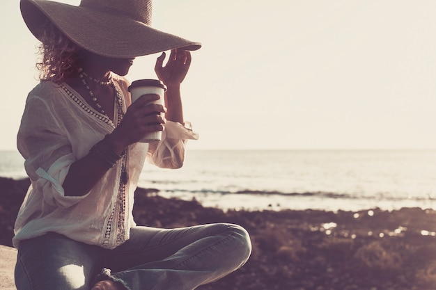 Concept van zomervakantie, vakantie, reizen en mensen - lachende vrouw in zonnehoed en kopje koffie of drinken op het strand met horizon en zee