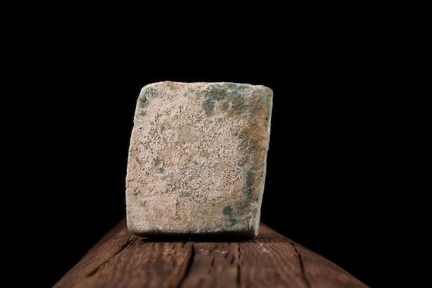 Concept - verlopen producten, onjuiste opslag. bedorven, beschimmelde kaas ligt op een oude houten plank.