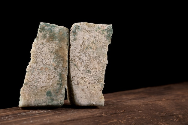 Concept - verlopen producten, onjuiste opslag. bedorven, beschimmelde kaas op een oude houten plank.