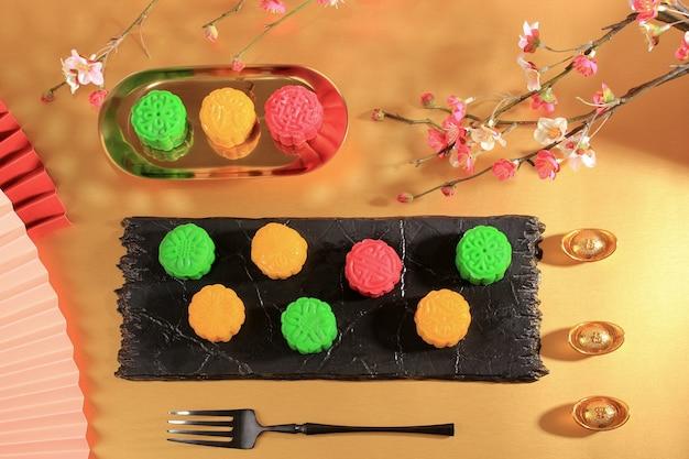 Concept verschillende mooncake, traditionele en kleurrijke snow skin moon cake, dessert voor mid-autumn festival op gouden achtergrond, close-up, lifestyle.
