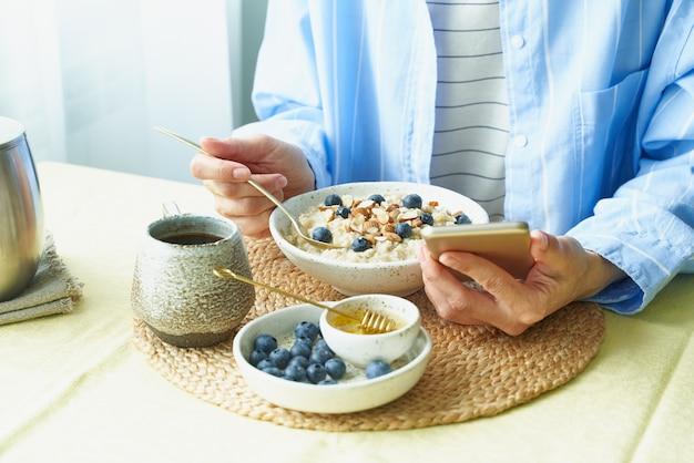 Concept voor digitale verslaving met mobiel, tijdens het ontbijt.