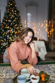 Concept voor kerstfotografie, gelukkige jonge vrouw in warme trui eten in donkere keuken