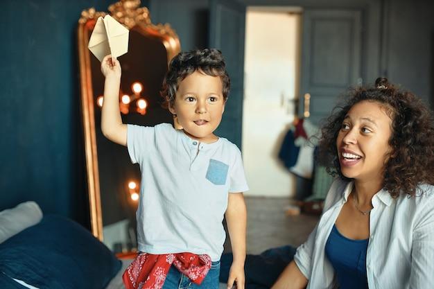 Concept voor kinderen, moederschap, plezier en hobby. indoor portret van opgewonden emotionele donkere huid jongetje staande op bed met hand omhoog