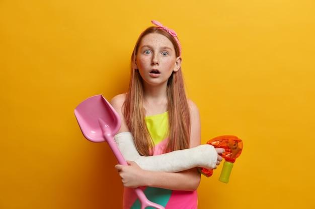 Concept voor kinderen, vrije tijd en spelletjes. geschokt meisje speelt waterpistool, houdt zandschop vast, heeft plezier aan zee tijdens de zomer, onder de indruk om te zien dat iets geweldigs een badpak op gewonde arm draagt