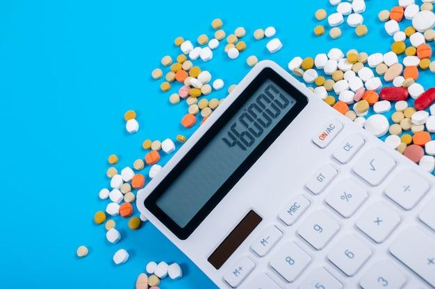 Concept voor medische kosten, tabletten en rekenmachines op een blauwe achtergrond