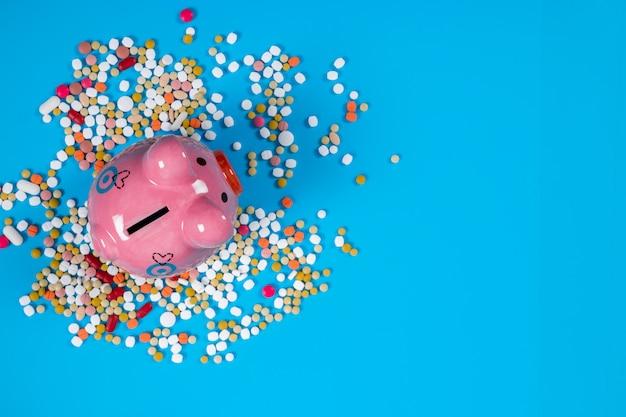 Concept voor medische kosten, tabletten en spaarvarken op blauwe achtergrond