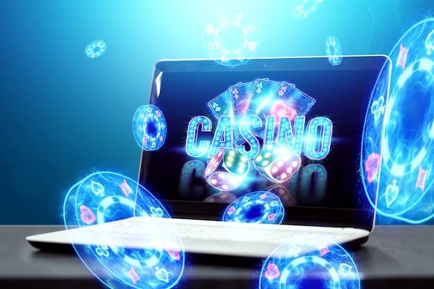 Concept voor online casino, gokken, online geldspellen, weddenschappen. neon casinofiches, casino-inscriptie, pokerkaarten, dobbelstenen vliegen uit de laptop.
