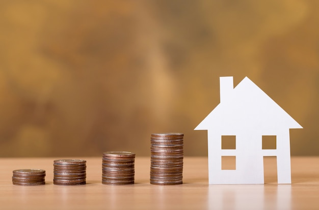 Concept voor onroerendgoedladder, papierhuis en muntenstapel om te sparen om een huis te kopen