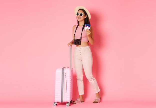 Concept voor toerisme, zomervakantie, vakanties in het buitenland. volledige lengte van trendy aziatische meisjestoerist, reiziger in hoed en zonnebril ingepakte koffer en bedrijfpaspoort met vluchttikkers, roze muur