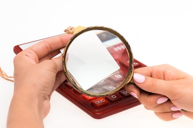 Concept voor winkelen op internet: handen met vergrootglas en prijskaartje