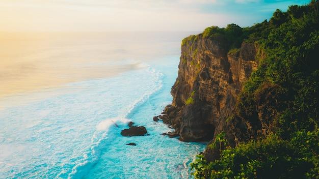 Concept vrijheid landschap - hoge rots klif strand met bomen en golven op zonsondergang
